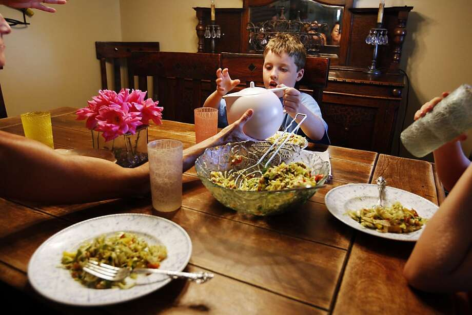 Keenan pours himself some water with the help of his mother during a nutritious family meal. He even learned to like salad. Photo: Rohan Smith, The Chronicle