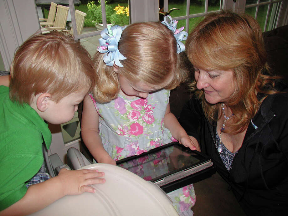 The Taylor children work on an iPad with Laurie Allan, a social worker of STAR Rubino Family Center. Photo: Contributed Photo
