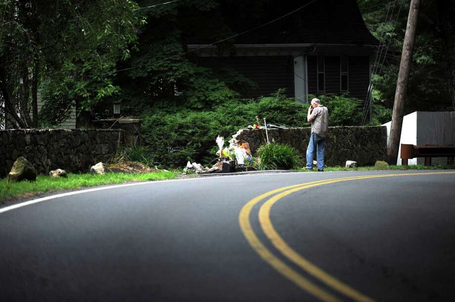 Flowers and ice hockey sticks are left Monday, July 22, 2013, on Riversville Road, where Vinny Scorese, 19,  a 2012 Greenwich High School graduate, died when his car  swerved off the road in Greenwich, Conn., early Saturday morning. Photo: Helen Neafsey / Greenwich Time
