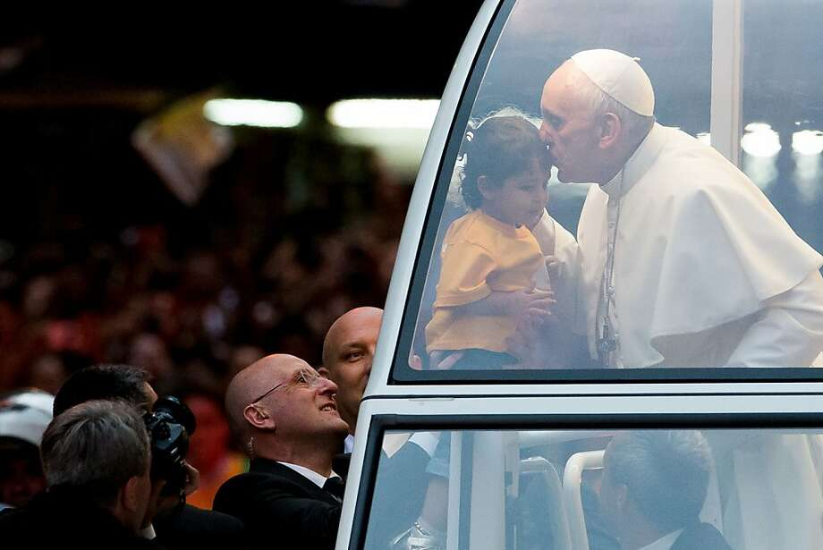 Pope Francis kisses a child lifted up to him after leaving Metropolitan Cathedral in Rio de Janeiro. Photo: Buda Mendes, Getty Images