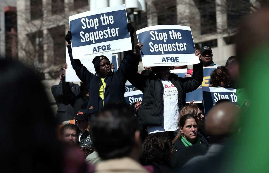 Federal employees protest budget cuts related to sequestration in front of the Department of Labor in March. This writer notes that military and civilian Defense Department employees have not been immune to the sequestration's impact. Photo: Win McNamee / Getty Images