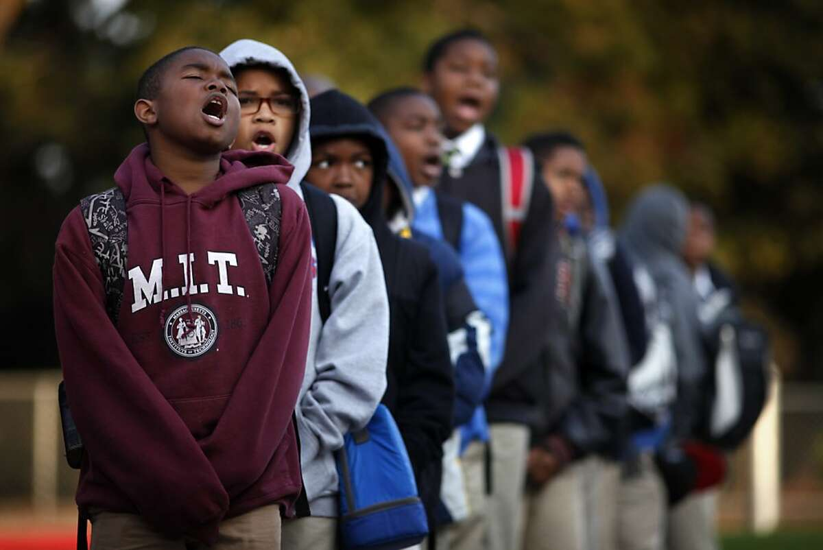 Imir Stills-Bey, left, Donavon Richard, and Kavion Hammond lead Mr. Peter Wilson's sixth grade class in the scholar holler at the start of school, Friday March 22, 2013, at the100 Black Men Community Charter School in Oakland, Calif.