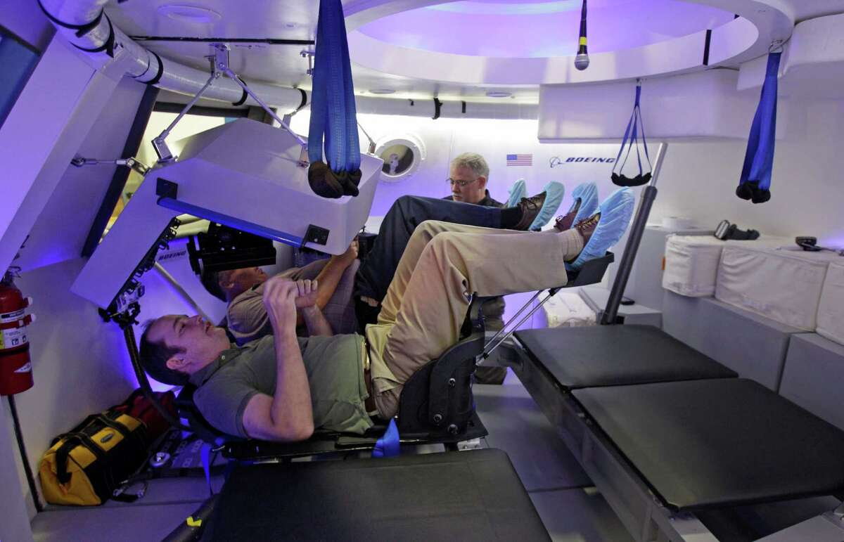 Houston Chronicle reporter Eric Berger tries out a seat inside a mock-up of the Boeing CST-100 capsule during a tour at Boeing, 13100 Space Center Boulevard, Monday, July 22, 2013, in Houston.