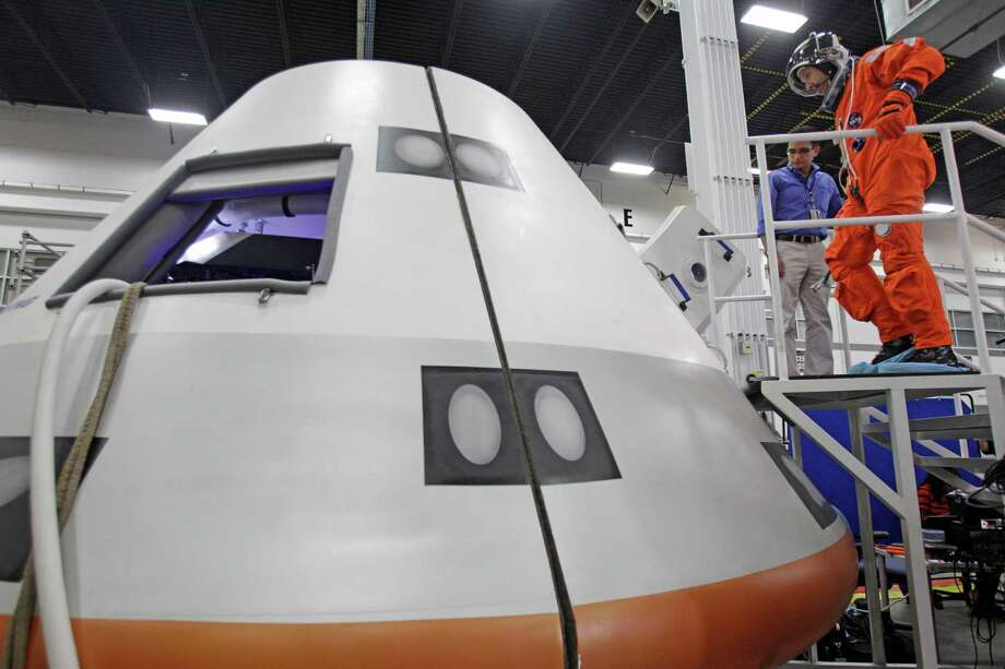 NASA Astronaut Randy Bresnik enters a mock-up of the Boeing CST-100 capsule for a flight suit evaluation at Boeing Houston Product Support Center, 13100 Space Center Boulevard, Monday, July 22, 2013, in Houston. Photo: Melissa Phillip, Houston Chronicle / © 2013  Houston Chronicle