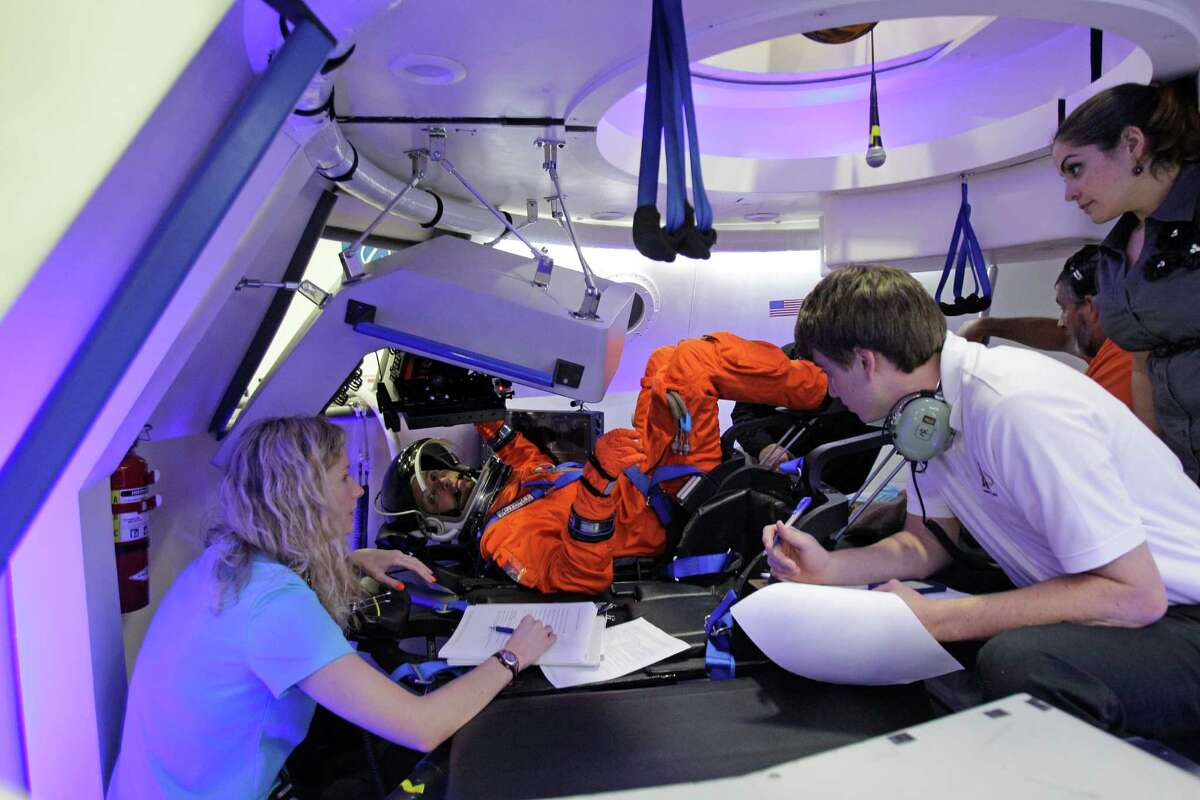 Boeing personnel talk with NASA Astronaut Randy Bresnik, center, inside a mock-up the Boeing CST-100 capsule during a flight suit evaluation at Boeing Houston Product Support Center, 13100 Space Center Boulevard, Monday, July 22, 2013, in Houston.