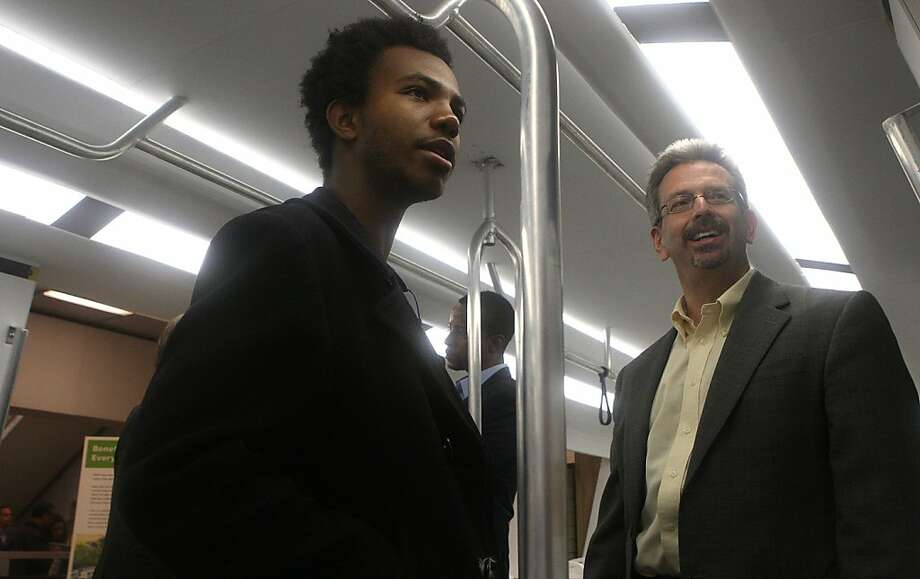 """Bashir Leathers (left), 17 years old, from Oakland is shown the """"Fleet of the Future"""" model train car by chief marketing officer Aaron Weinstein (right) during a preview at MacArthur Bart station in Oakland, Calif., on Monday, July 22, 2013.  Leathers questions energy use between the present and future trains.  The preview of Bart's """"Fleet of the Future"""" model train car will be open for public viewing from Tuesday to Friday. Photo: Liz Hafalia, The Chronicle"""