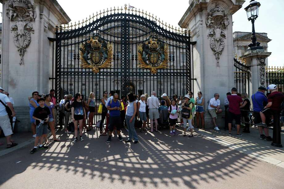 People look at Buckingham Palace in London where a notice announcing the birth of the baby will be posted, Monday, July 22, 2013. Buckingham Palace officials say Prince William's wife, Kate, Duchess of Cambridge, has been admitted to St Mary's Hospital in the early stages of labour. Photo: Sang Tan