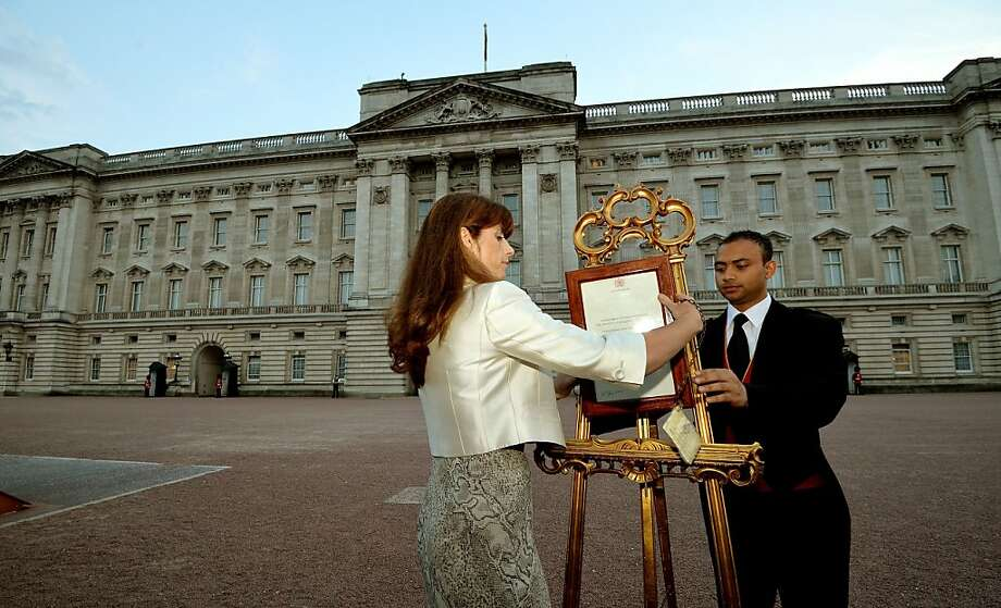 The Queen's Press Secretary Ailsa Anderson with Badar Azim, a footman, places an official document to announce the birth of a baby  boy, at 4.24pm to the William and Kate, the Duke and Duchess of Cambridge at St Mary's Hospital,  in the forecourt of Buckingham Palace in London Monday July 22, 2013. The child is now third in line to the British throne.  (AP Photo/John Stillwell, Pool) Photo: John Stillwell, Associated Press
