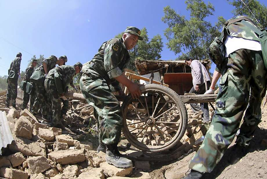 Chinese paramilitary policemen help residents remove belongings from damaged houses in Lalu village of Hetuo township in Minxian in northwest China's Gansu province. Photo: Associated Press
