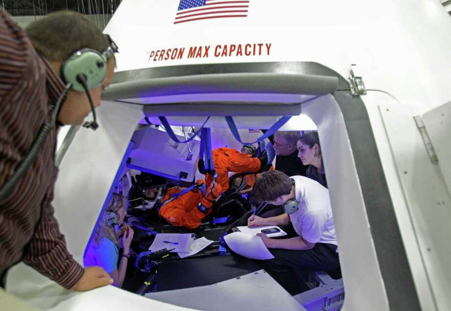 Boeing personnel talk with NASA Astronaut Randy Bresnik, center, inside a mock-up of the Boeing CST-100 capsule during a flight suit evaluation at the Boeing Houston Product Support Center, 13100 Space Center Boulevard. Photo: Melissa Phillip, Staff / © 2013  Houston Chronicle