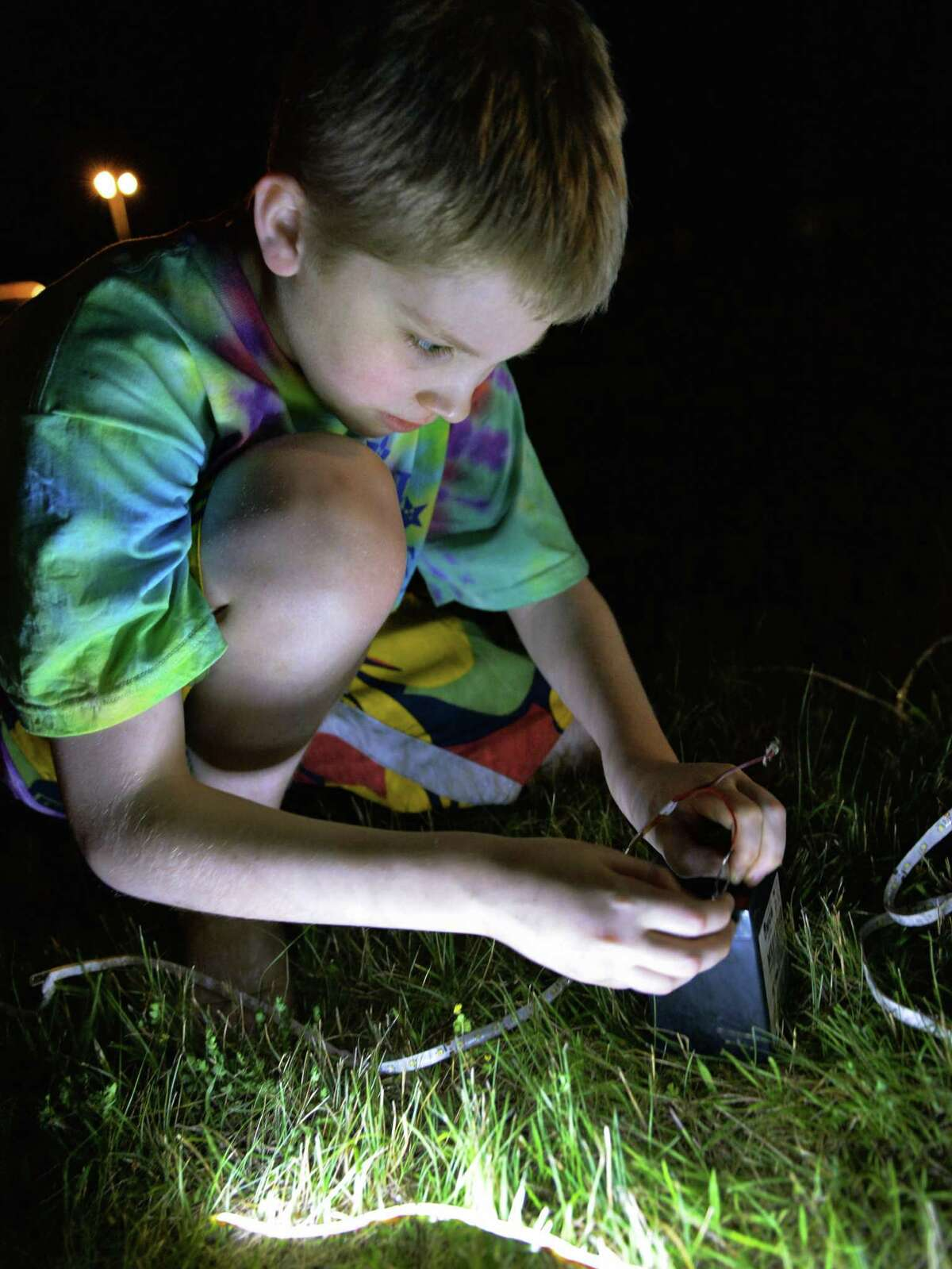 Mackinly Adams, 13, of Pittsburgh, Penn., who suffers from a rare skin disease that makes it dangerous for him to be exposed to sunlight, hooks up a string of LED lights at Camp Sundown in Craryville, N.Y., Friday night July 12, 2013. (John Carl D'Annibale / Times Union)