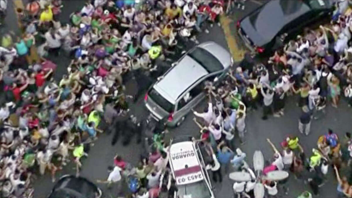 In this image from video, a crowd mobs the silver Fiat carrying Pope Francis through Rio de Janeiro on Monday, July 22, 2013. Ecstatic believers forced the closed Fiat to stop several times as they swarmed around during the drive from the airport to an official opening ceremony in the center of the city. (AP Photo) ORG XMIT: NY201