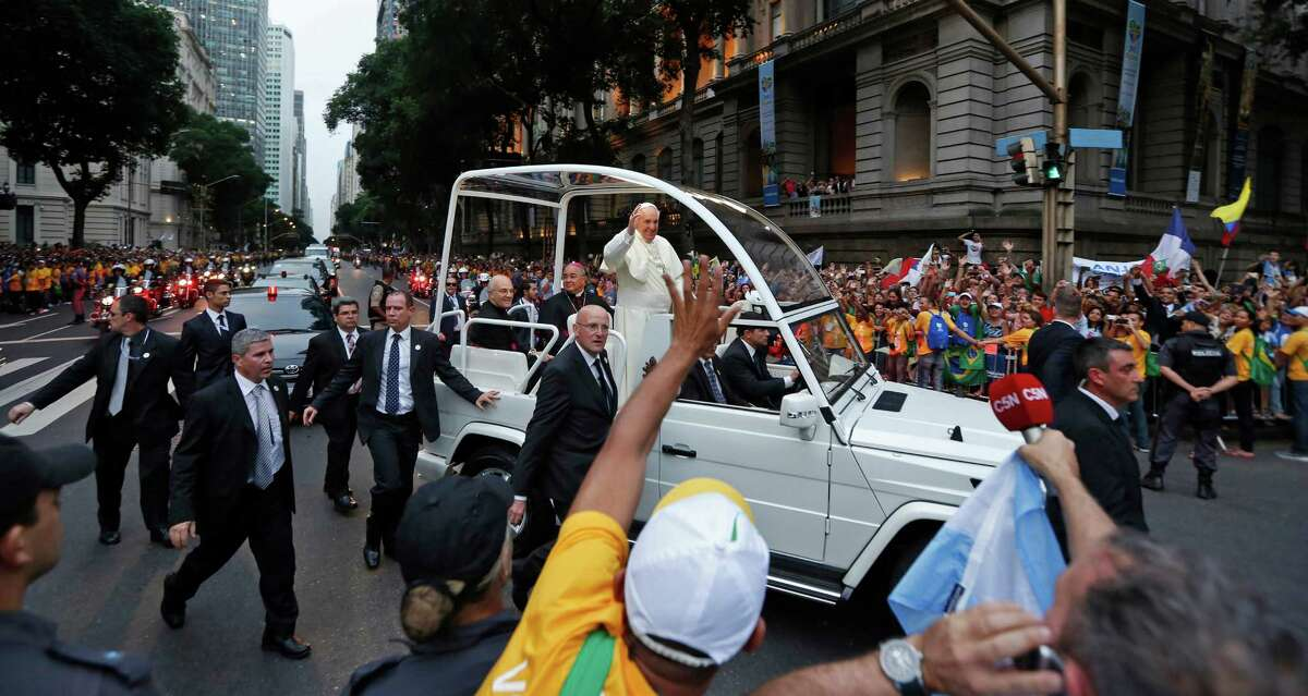 A crowd of faithful cheer as Pope Francis rides in his popemobile in Rio de Janeiro, Brazil, Monday July 22, 2013. The pontiff arrived for a seven-day visit in Brazil, the world's most populous Roman Catholic nation. During his visit, Francis will meet with legions of young Roman Catholics converging on Rio for the church's World Youth Day festival. (AP Photo/Victor R. Caivano) ORG XMIT: VC104