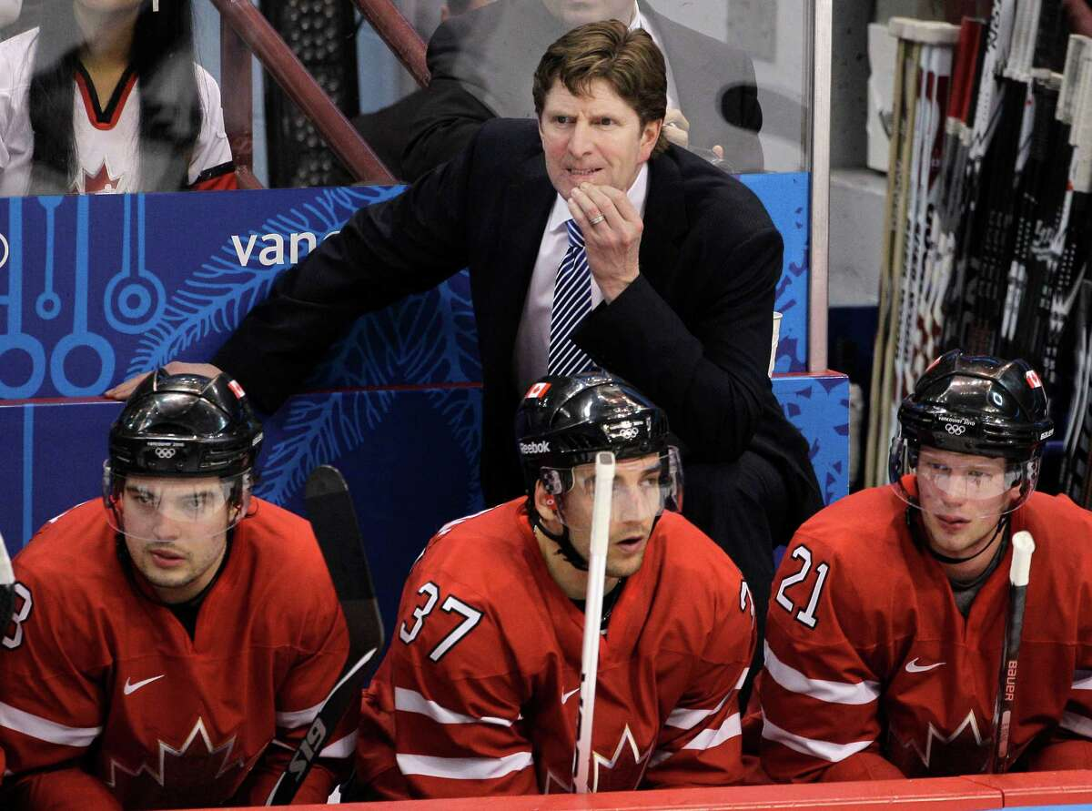 FILE - In this Feb. 23, 2010 file photo, Canada head coach Mike Babcock watches as his team plays Germany in the second period of a men's playoff qualifying round ice hockey game at the Vancouver 2010 Olympics in Vancouver, British Columbia. Seated are Drew Doughty, left, Patrice Bergeron (37), and Eric Staal (21). Babcock will return as coach of Canada's Olympic hockey team. Monday's, July 22, 2013, announcement by Hockey Canada comes after an agreement was reached to have NHL players participate in Russia. (AP Photo/Mark Humphrey, File) ORG XMIT: NY153