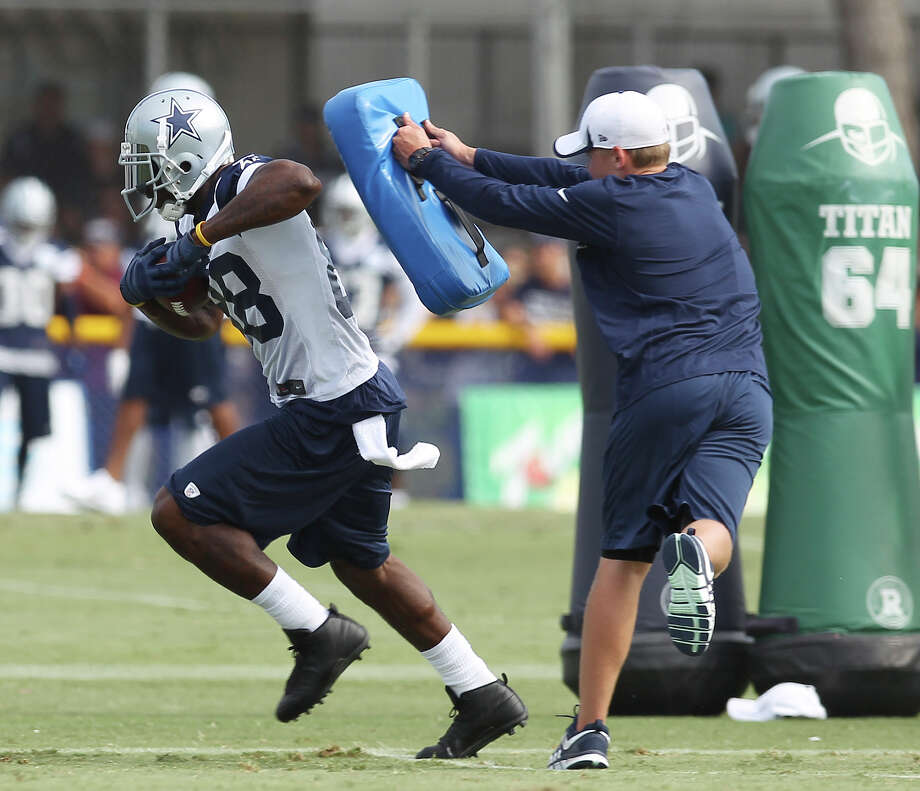 Receiver Dez Bryant runs past a blocking pad during the afternoon session of the 2013 Dallas Cowboys training camp on Monday, July 22, 2013 in Oxnard. Photo: Kin Man Hui, San Antonio Express-News / ©2013 San Antonio Express-News