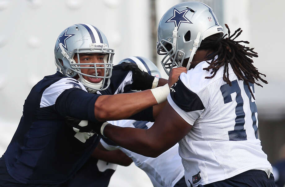 Defensive end Ben Bass (left) tangles with offensive lineman Edawn Coughman (76) during the afternoon session of the 2013 Dallas Cowboys training camp on Monday, July 22, 2013 in Oxnard. Photo: Kin Man Hui, San Antonio Express-News / ©2013 San Antonio Express-News