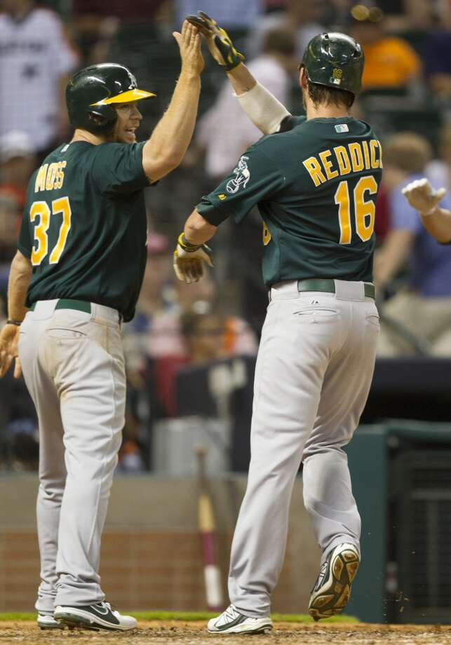 Josh Reddick of the A's is congratulated by teammate Brandon Moss after hitting a two-run home run in the eight inning . Photo: J. Patric Schneider, For The Chronicle