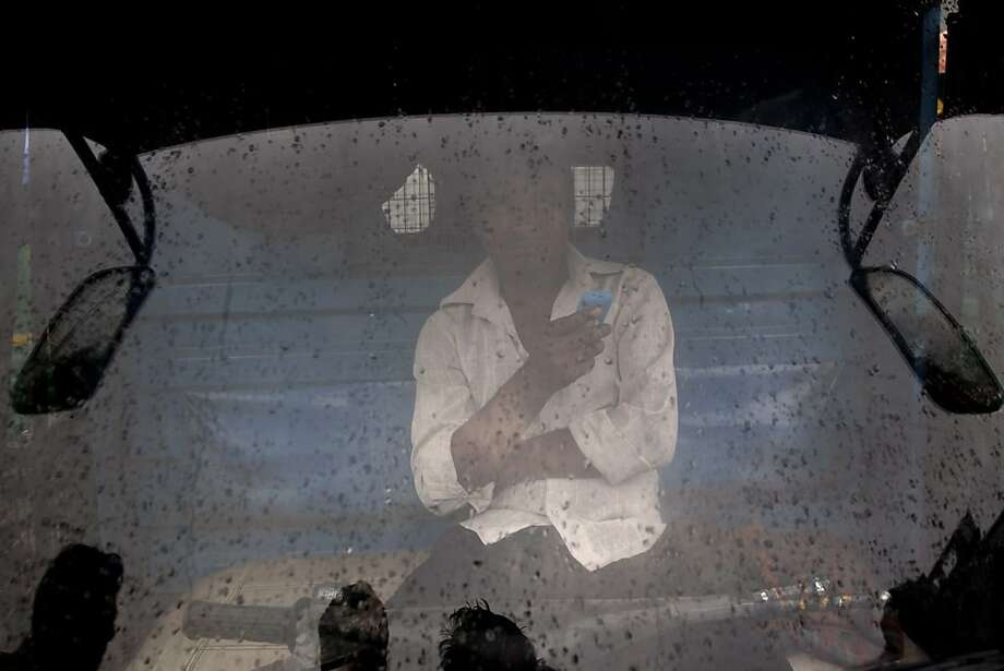 An Indian man looks out from the wind shield of his truck as it rains in New Delhi, India, Monday, July 22, 2013. Heavy rains hit the capital Monday causing major traffic disruptions due to water-logging of streets. (AP Photo/Tsering Topgyal) Photo: Tsering Topgyal, Associated Press