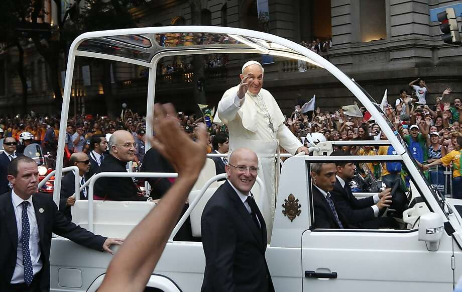 Pope Francis waves from his popemobile as he makes his way into central Rio de Janeiro, Brazil, Monday, July 22, 2013. The pontiff arrived for a seven-day visit in Brazil, the world's most populous Roman Catholic nation. During his visit, Francis will meet with legions of young Roman Catholics converging on Rio for the church's World Youth Day festival. (AP Photo/Victor R. Caivano) Photo: Victor R. Caivano, Associated Press