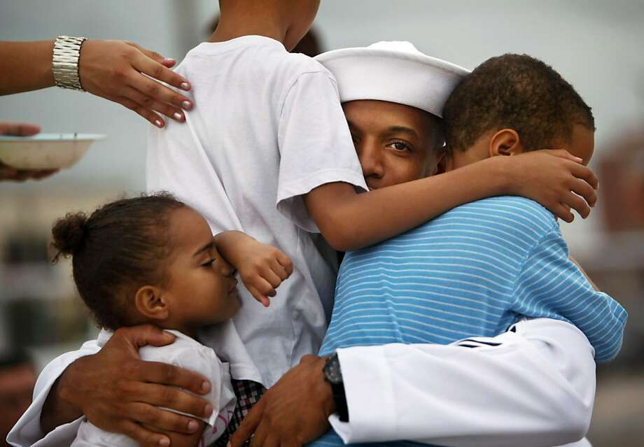 Petty Officer 1st Class Malik Leslie hugs his children, from left, Layla, 3, Malik, 7, and Seth, 5, before his deployment on the Harry S. Truman from Norfolk Naval Station, Va., for a nine-month cruise to the Persian Gulf on Monday, July 22, 2013.  (AP Photo/The Virginian-Pilot, Stephen M. Katz) Photo: Stephen M. Katz, Associated Press