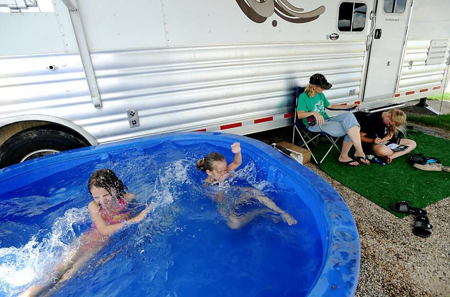 From left, Cassidy McLaughlin and Mikayla Kinslow splash around a pool, as Mikayla's mother Paula Kinslow and sister Tara Kinslow sit in front of a friend's trailer at the 2013 State 4-H Horse Show at the Taylor County Expo Center Monday, July 22, 2013, in Abilene, Texas. (AP Photo/Abilene Reporter-News, Nellie Doneva) Photo: Nellie Doneva, Associated Press