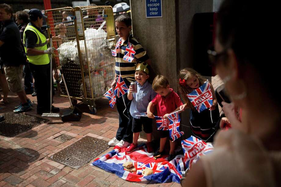 An impromptu picnic is had by children as supporters await the departure of Britain's Prince William, Kate, Duchess of Cambridge and the Prince of Cambridge, outside the entrance of the private Lindo Wing at St. Mary's Hospital in London, Tuesday, July 23, 2013. It's Day One of parenting for Prince William and Kate. After the excitement and fatigue and joy of childbirth, emotions shared with a nation, the young couple is expected to bring the prince home Tuesday. Photo: Matt Dunham