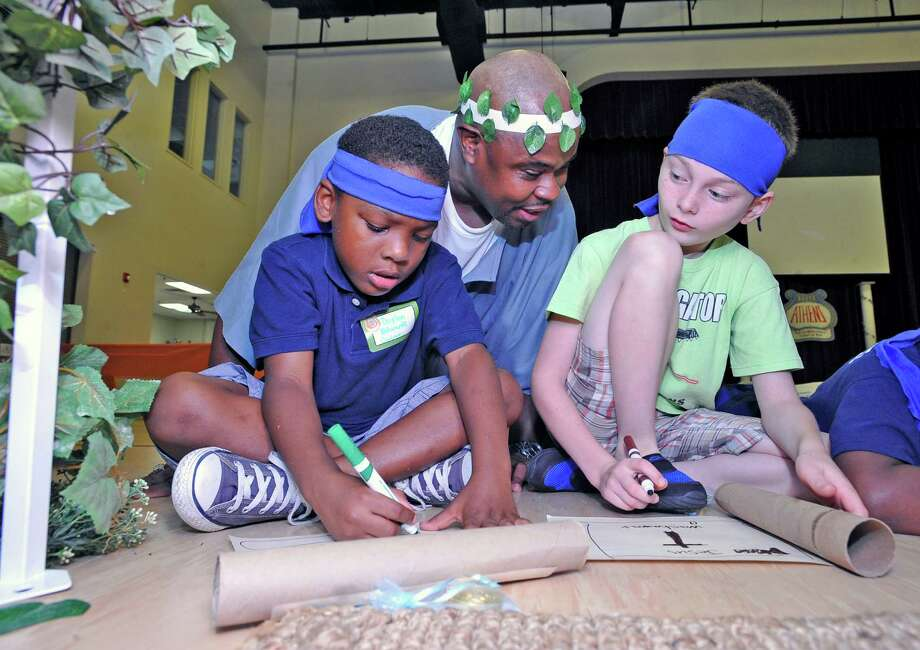 "Reverand Demetrius Moffett, center, helps Daylen Edwards, left and Aidan Garnon, right with writing of their scrolls about what they know about Jesus and the Apostle Paul.  The First Church of Nazarene, Orange has partnered with three other churches for vacation bible school this summer. Out of the four churches, they are expecting about 200 children, ages 5-14, to attend. With the help of a lot of adults, each group got to visit a different ""station"" to learn about Jesus. The VBS is being held at First United Methodist Church.   Dave Ryan/The Enterprise"