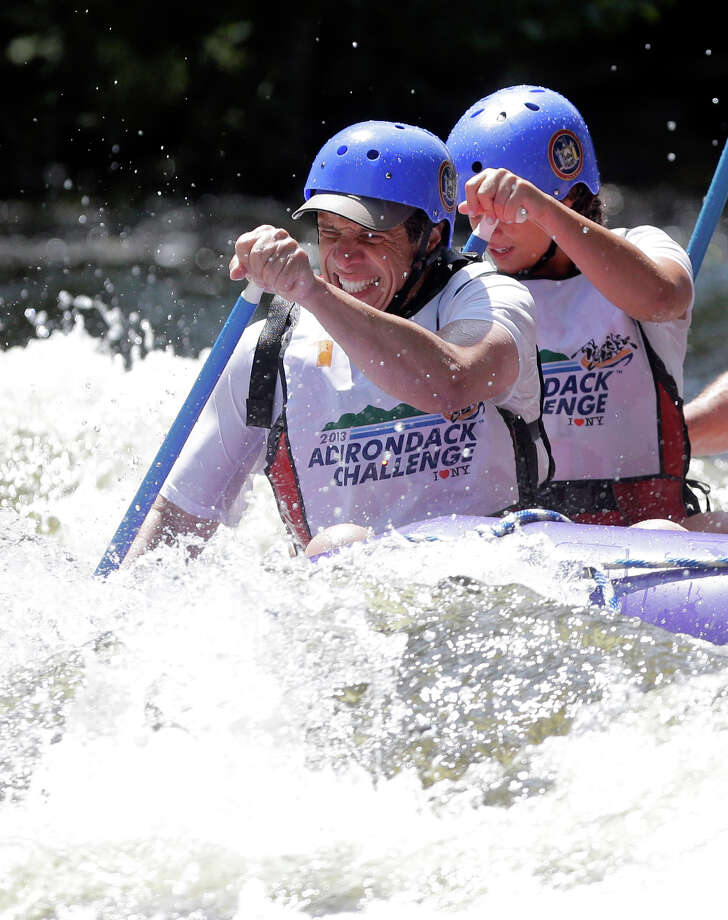 New York Gov. Andrew Cuomo and his team navigate whitewater rapids in a raft on the Indian River during the Adirondack Challenge on Monday, July 22, 2013, in Indian Lake, N.Y. The event was held to draw attention to recreational opportunities in the Adirondacks and boost tourism. (AP Photo/Mike Groll) ORG XMIT: NYMG104 Photo: Mike Groll, AP / AP