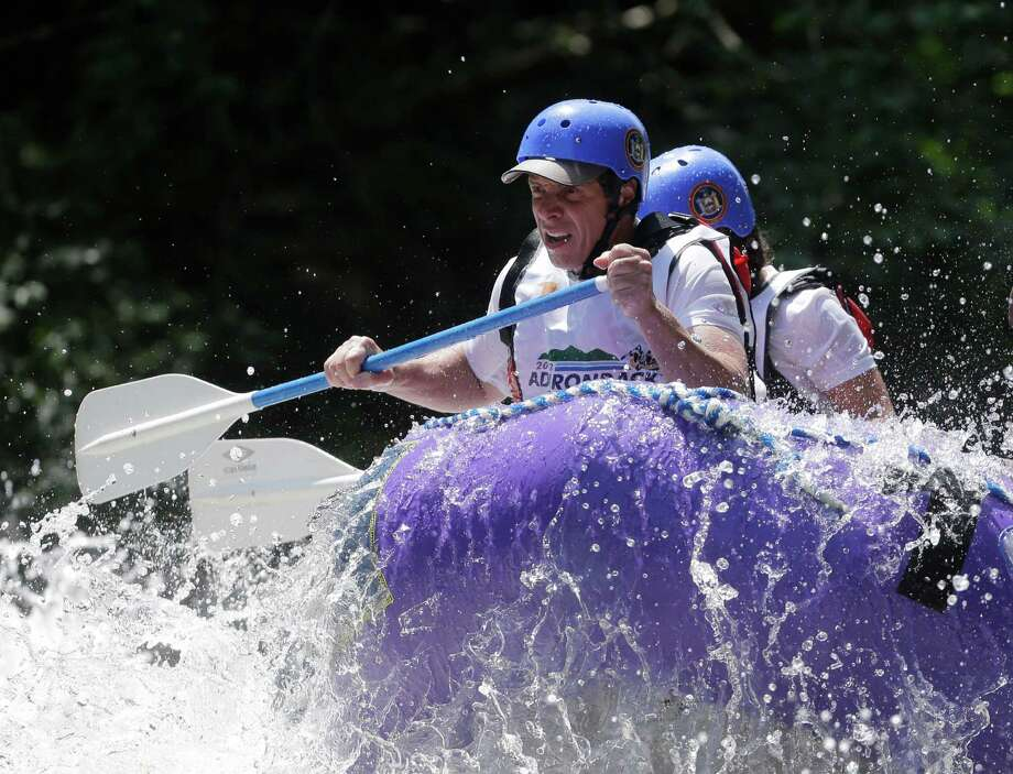 New York Gov. Andrew Cuomo and his team navigate whitewater rapids in a raft on the Indian River during the Adirondack Challenge on Monday, July 22, 2013, in Indian Lake, N.Y. The event was held to draw attention to recreational opportunities in the Adirondacks and boost tourism. (AP Photo/Mike Groll) ORG XMIT: NYMG103 Photo: Mike Groll, AP / AP