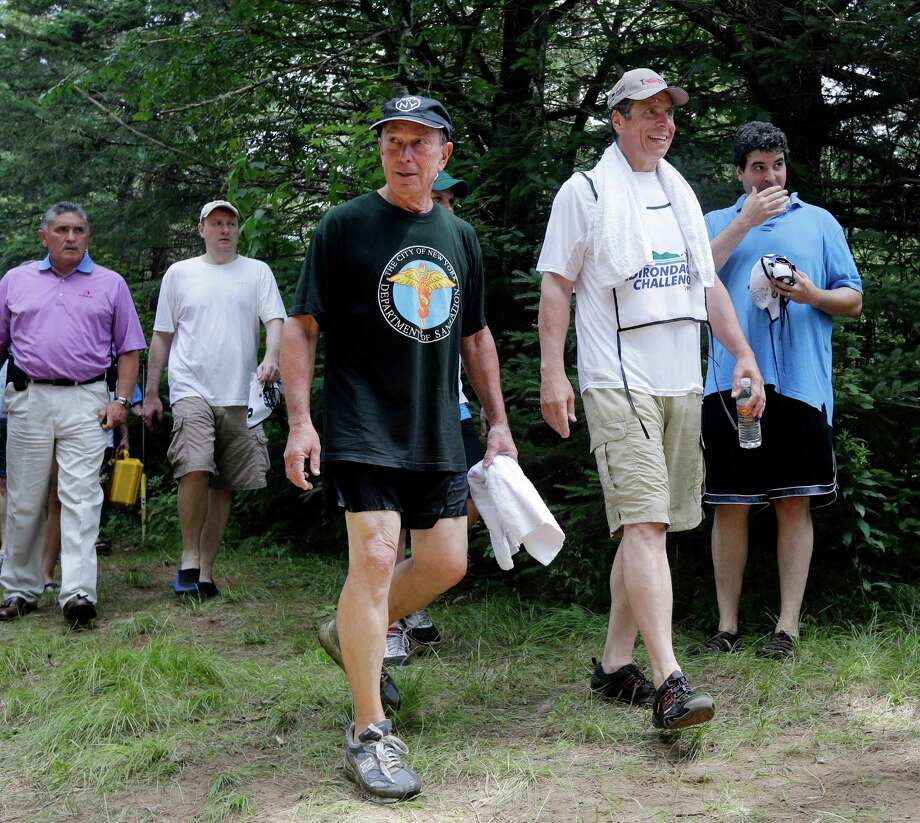 New York City Mayor Michael Bloomberg, left, and New York Gov. Andrew Cuomo walk to their vehicles after competing in the Adirondack Challenge on the Indian River on Monday, July 22, 2013, in Indian Lake, N.Y. The event was held to draw attention to recreational opportunities in the Adirondacks and boost tourism. (AP Photo/Mike Groll) ORG XMIT: NYMG108 Photo: Mike Groll, AP / AP