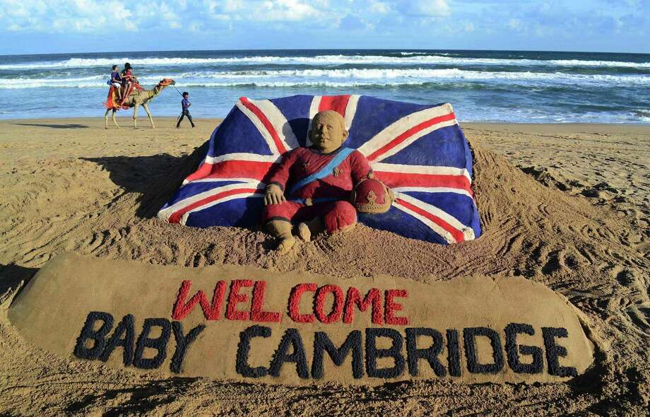 Tourists ride a camel past a sand sculpture created by sand artist Sudarshan Pattnaik to celebrate the birth of the Prince of Cambridge, the son of Britain's Prince William and Kate, Duchess of Cambridge, at a beach in Puri, India, Tuesday, July 23, 2013. Photo: AP