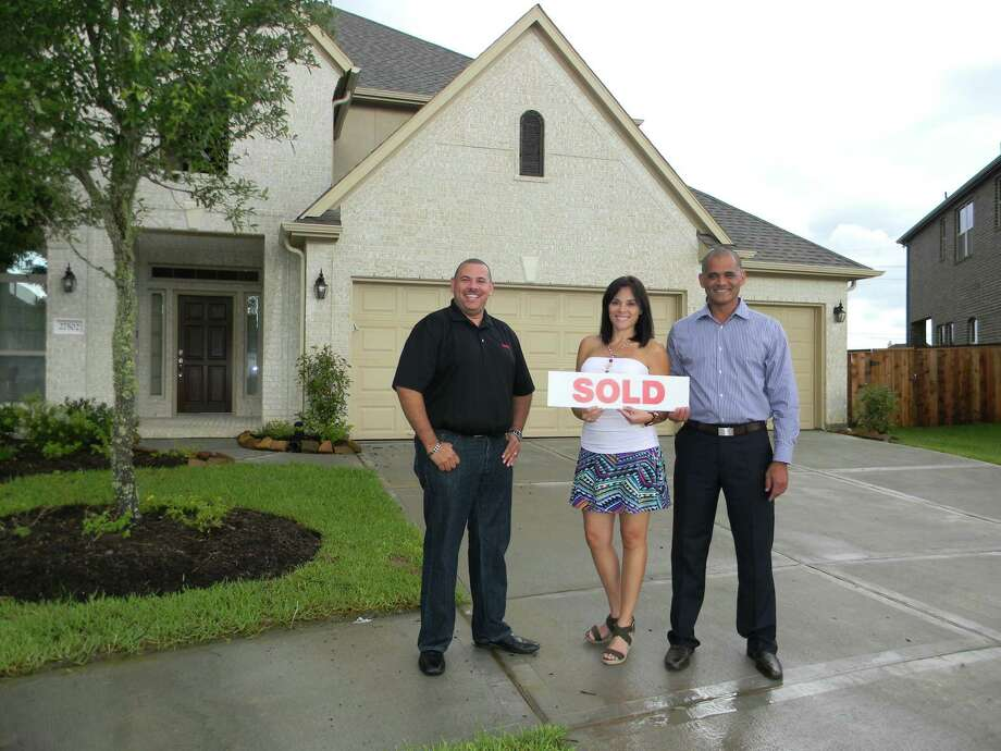 RE/MAX Prestige agent Mario Negron is busy selling homes in CyFair's thriving real estate market. Negron is pictured with Laura and Lisandro Roman. Photo: Picasa