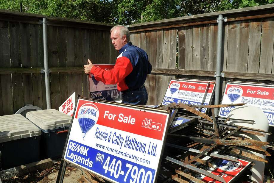 Ronnie Matthews moves one of his for sale signs at the Ronnie and Cathy Matthews Re/Max office, 5910 FM 2920 in Spring. The Matthews are a long-time team in the north Houston area. Photo by David Hopper Photo: David Hopper, Freelance / freelance