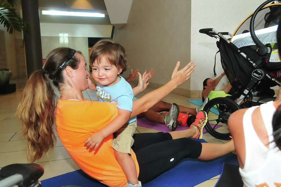 Liz Aldape works out with her son Isaac, 2, during Baby Boot Camp at Memorial City Mall. Photo: Â Tony Bullard 2013, Freelance Photographer / © Tony Bullard & the Houston Chronicle
