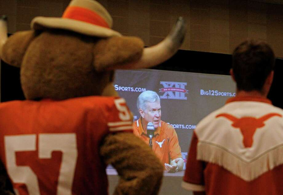 Members of theTexas cheerleading squad watch Texas football coach Mack Brown address the media during the Big 12 Conference Football Media Days Monday, July 23, 2013 in Dallas.  (AP Photo/Tim Sharp) Photo: TIM SHARP, Associated Press / FR62992 AP