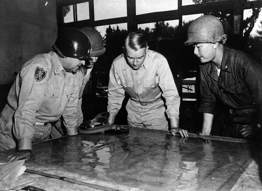 United States Army Chief of Staff General Collins studying a map of the front line during the battle for Korea, with Lieutenant General Walker, Brigadier General Farrell and Korean Brigadier General Paik. Photo: Keystone, Getty Images / Hulton Archive