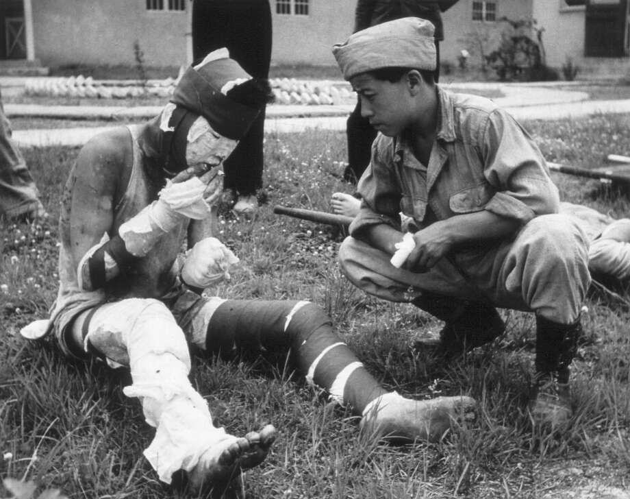 A severely wounded Korean soldier smoking a cigarette in the grounds of an advance casualty cleaning unit. Photo: Haywood Magee, Getty Images / Picture Post
