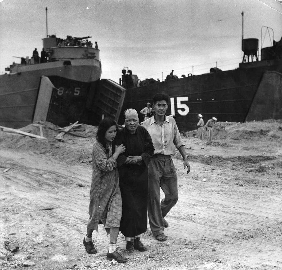 A civilian casualty arrives on the beach at Inchon in South Korea to see the US medical officer during the Korean War. US amphibious craft used in the invasion are in the background. Photo: Bert Hardy, Getty Images / Picture Post