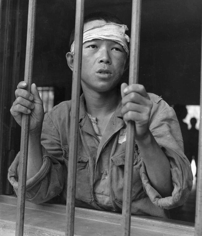 A prisoner staring through the bars at Taegu POW camp in Korea. Photo: Picture Post, Getty Images / Picture Post