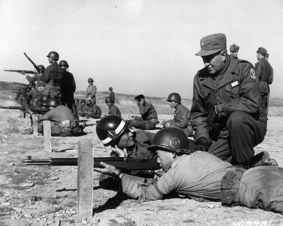 Major Harry Hoffman watching target practice at a Korean training area. Photo: Central Press, Getty Images / Hulton Archive