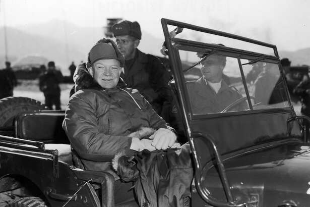 President Elect Dwight Eisenhower (1890 - 1969) and General Mark Clark (back seat, 1896 - 1984), in a jeep during their tour of installations of the 2nd US Infantry Division on a visit to United Nations units along the fighting front during the Korean War.