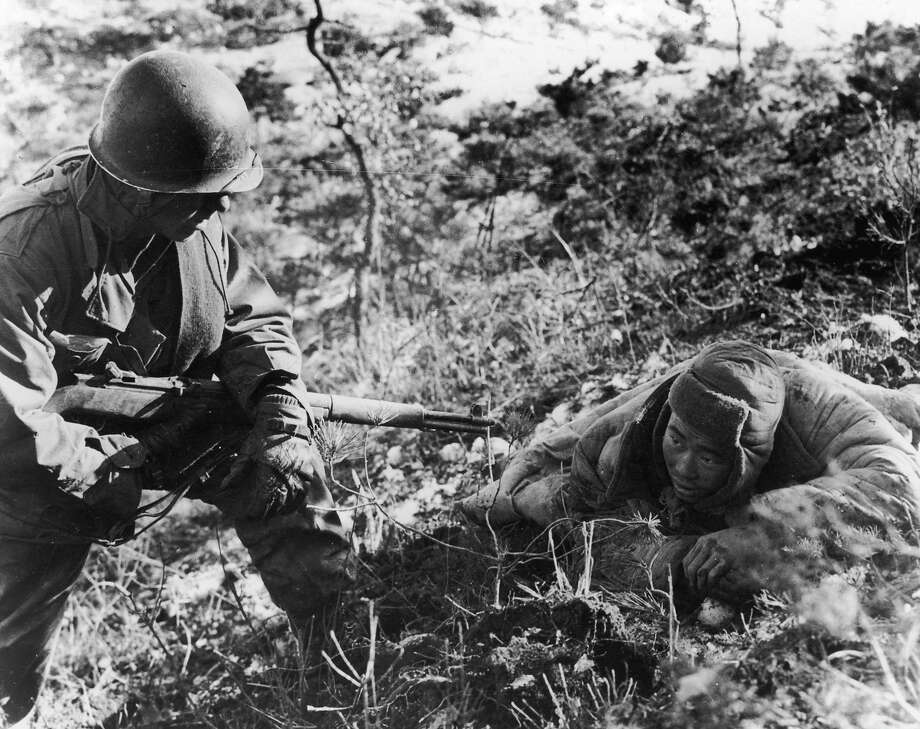 An American soldier taking a communist prisoner during the Korean war. Photo: Keystone, Getty Images / Hulton Archive