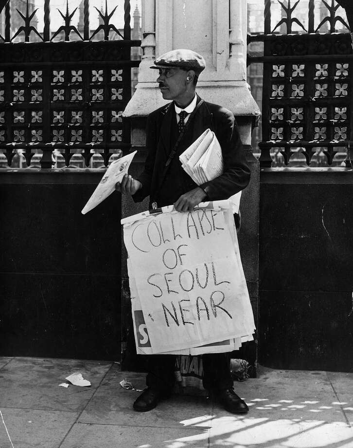 A newspaper seller in London's Westminster holds a billboard announcing 'Collapse of Seoul Near', two days after the start of the Korean War. Photo: Spooner, Getty Images / Hulton Archive