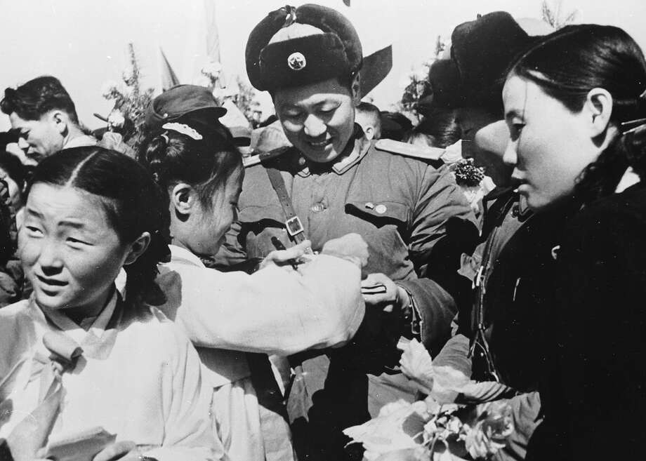 Korean girls present a member of the Chinese People's Volunteer Army with a bouquet of flowers prior to the mass withdrawal of Chinese troops from North Korea. Photo: Keystone, Getty Images / Hulton Archive