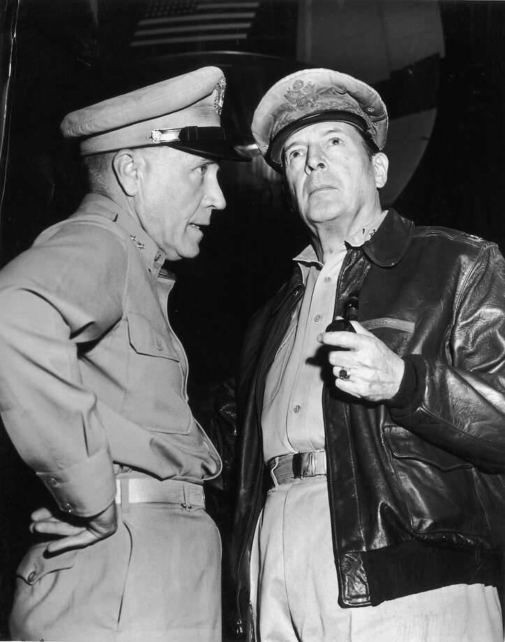 American military leaders General Hickey (L) and General Douglas MacArthur (1880 - 1964) talk at an airport in Korea. MacArthur is wearing a leather bomber jacket and is holding a pipe. Photo: Hulton Archive, Getty Images / Archive Photos