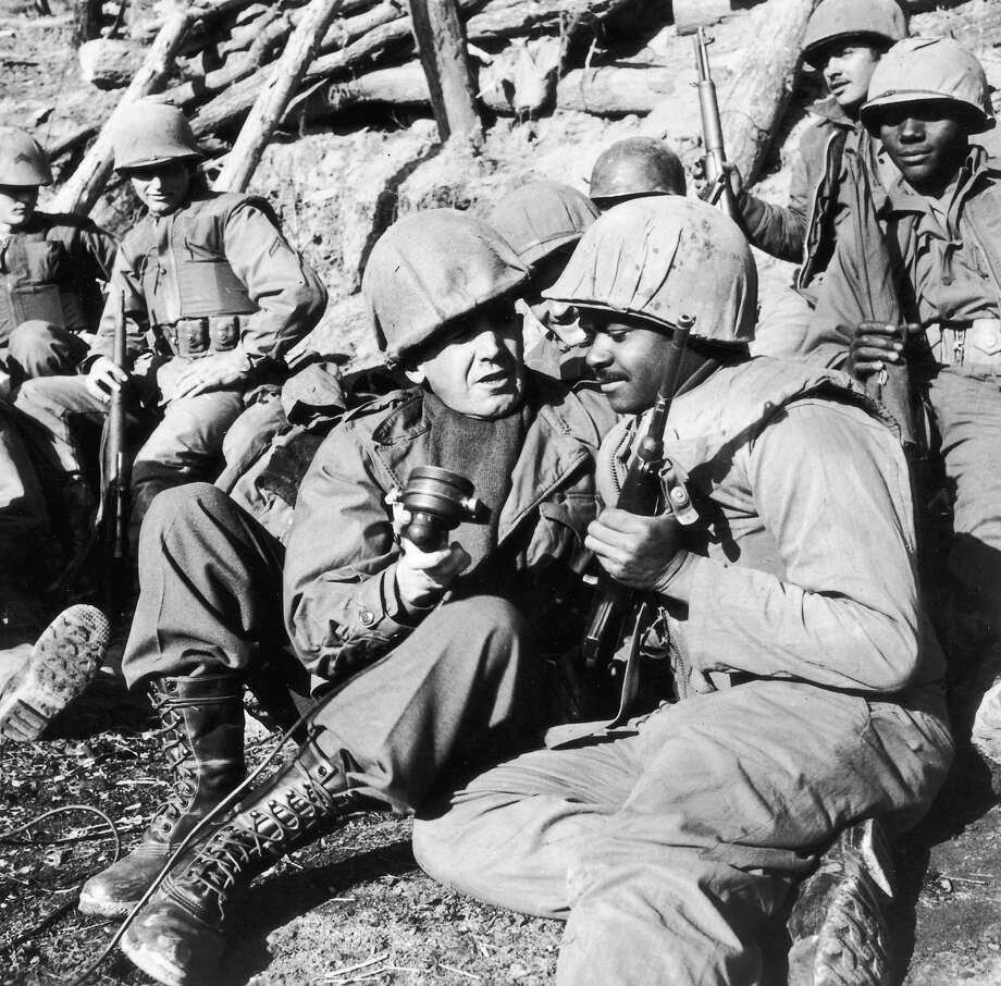 American broadcast journalist Edward R. Murrow (C) sits in a trench with a microphone in his hand, interviewing an African-American US Marine during the Korean War for his CBS television show 'See It Now,' Korea. The  company was holding a ridge on the Korean Front. Photo: Hulton Archive, Getty Images / Archive Photos