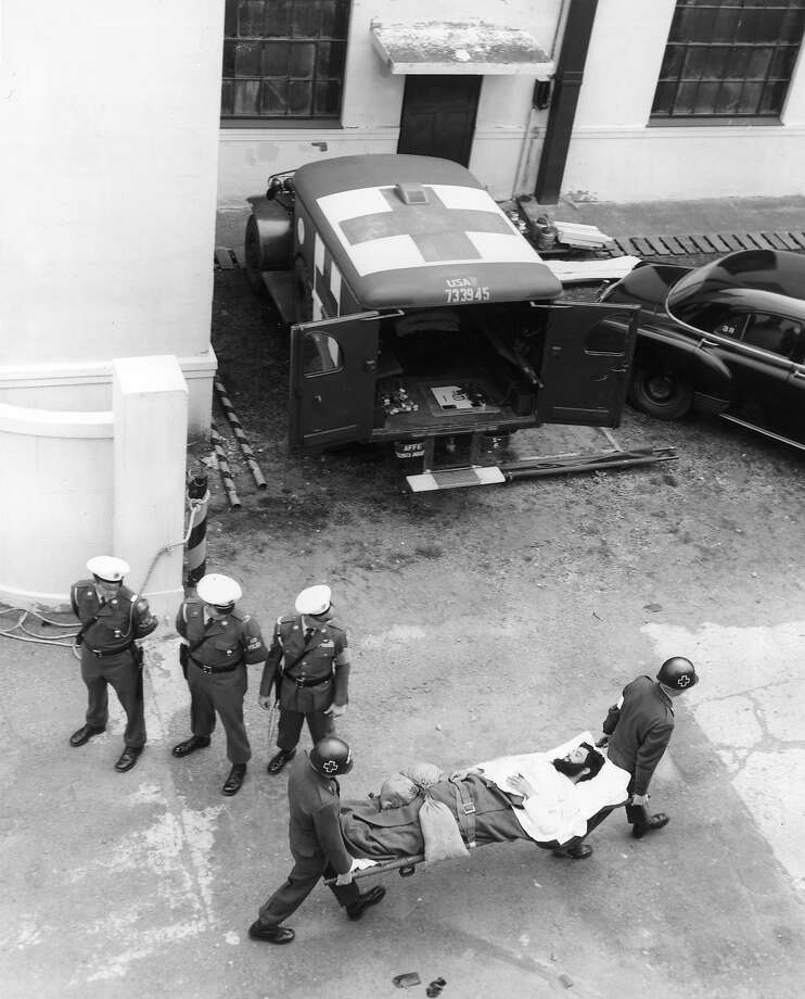 Aerial view of two Red Cross workers carrying an American POW on a stretcher toward an ambulance as three military policemen look on, Korea. Photo: Hulton Archive, Getty Images / Archive Photos