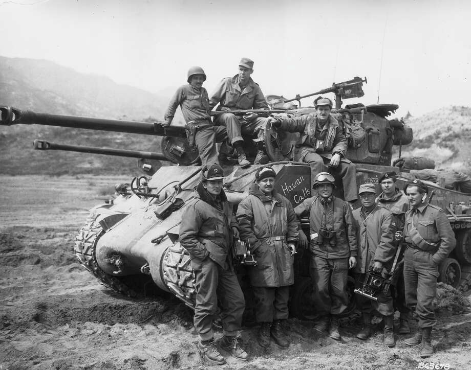 Group portrait of an American radio photo crew posed on and around a tank with 'Hawaii Calls' written on the side, during the Korean War, Korea. Several of the men hold their cameras. The crew transmitted coverage of the conflict to Tokyo. Photo: U.S. Army, Getty Images / Archive Photos