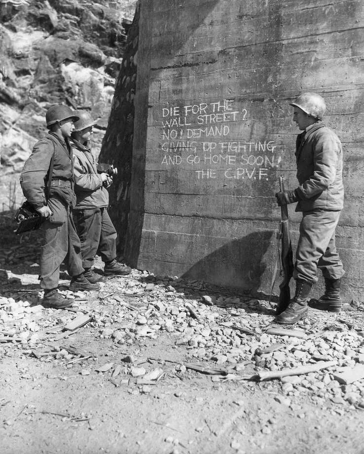 United Nations soldiers read propaganda written, in English, by Communist forces, on a wall near an underpass during the Korean War, Korea.  Two of the men hold cameras. The message urges the United Nations forces not to 'die for Wall Street,' and to give up the battle and return home. Photo: U.S. Army, Getty Images / Archive Photos