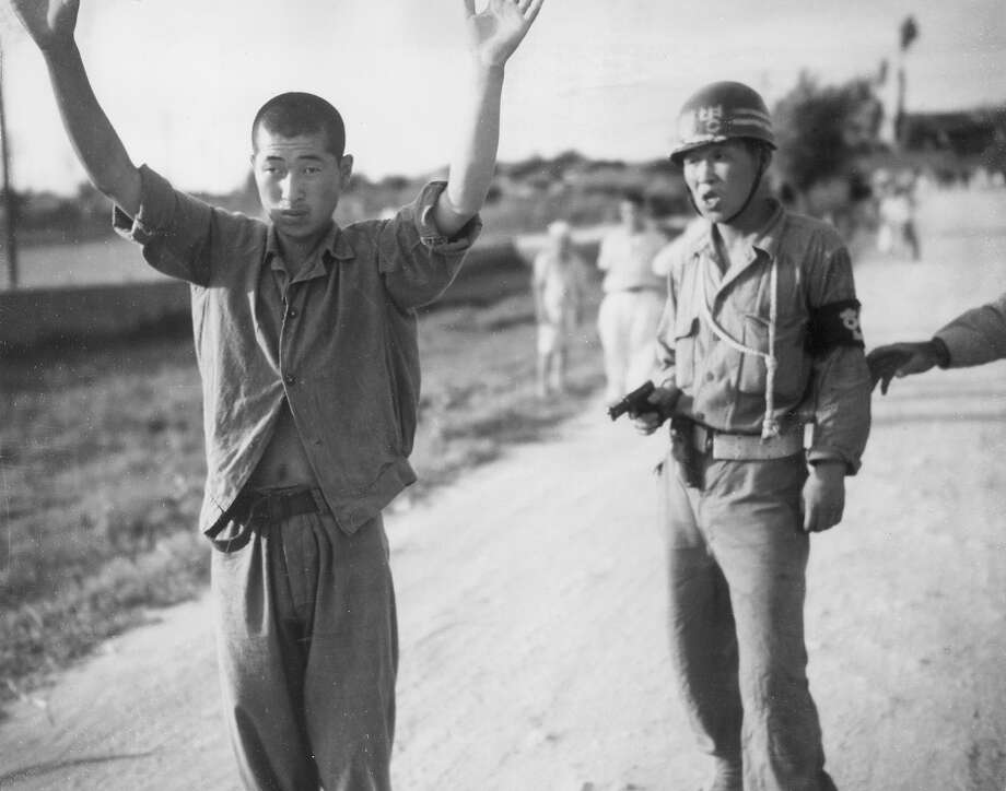 circa 1953:  A South Korean policeman holds a North Korean prisoner of war at gun point as he marches him to a stockade during the Korean War. Photo: Hulton Archive, Getty Images / Archive Photos
